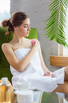 Giornata della bellezza. donna che fa la sua routine quotidiana di cura della pelle a casa