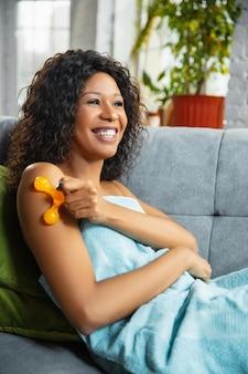 美容の日。自宅で毎日のスキンケアルーチンをしているタオルを着ている女性。ソファに座って、化粧品のローラーで手の肌をマッサージし、笑顔で。