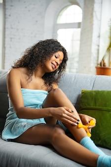 美容の日。自宅で毎日のスキンケアルーチンをしているタオルを着ている女性。ソファに座って、化粧品のローラーで足の皮膚をマッサージし、笑顔で。美容、セルフケア、化粧品、若者の概念。
