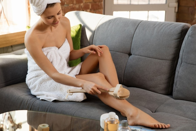 Beauty day. woman wearing towel doing her daily skincare routine at home. putting on moisturizing, doing anti-cellulite, lymphatic drainage massage. concept of beauty, self-care, cosmetics, youth.