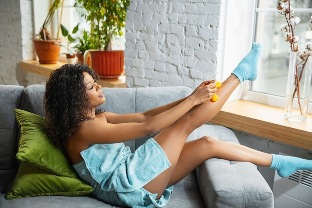 Beauty day. woman wearing towel doing her daily skincare routine at home. sitting on sofa, massaging legs' skin with cosmetic's roller, smiling. concept of beauty, self-care, cosmetics, youth.