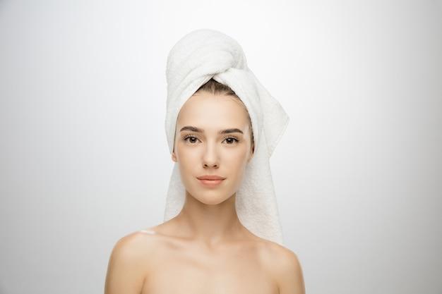 美容の日。白いスタジオの壁に隔離されたタオルを着ている女性。