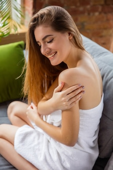 Beauty day for yourself. long haired woman wearing towel doing her daily skincare routine at home. sits on sofa, putting on moisurizer on shoulders' skin. concept of beauty, self-care, cosmetics.