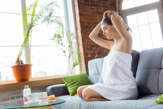 Beauty day for yourself. long haired woman wearing towel doing her daily skincare routine at home. sits on sofa, styling her hairstyle like ponytail. concept of beauty, self-care, cosmetics.