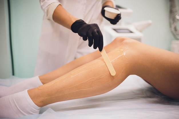 Beauty, depilation, epilation, hair removal and people concept - beautiful woman with applicator applying depilatory wax to her leg.