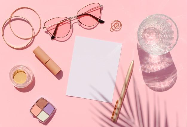 Вид сверху рабочего стола красоты с косметикой, тенями пальм и листом бумаги