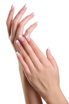 白で隔離されるフランス語マニキュアで美容エレガントな女性の手