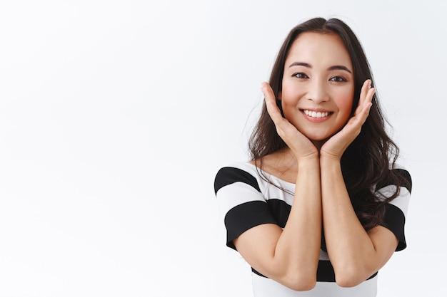 Concetto di bellezza, emozioni e cosmetologia. attraente, bella giovane ragazza asiatica che tocca la pelle pura, pulita senza imperfezioni e sorridente, dall'aspetto adorabile e deliziato, in piedi sciocco sfondo bianco