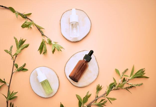 葉を使ったスキンケアレイアウト用のナチュラルオーガニック化粧品オイルとセラム。バイオサイエンスは、ブランディングとラベルのためのbeauty.emptyガラスボトルのコンセプトです。