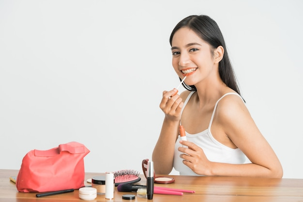 Beauty face of asian woman. portrait of female applying lipstick on her face close up