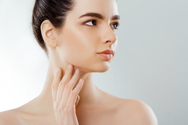 아름다움 얼굴. 자연스러운 메이크업으로 아름 다운 여자는 자신의 얼굴을 터치합니다. 확대. 미용술. 피부 관리.