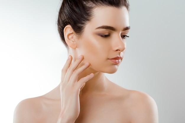아름다움 얼굴. 자연스러운 메이크업으로 아름 다운 여자는 자신의 얼굴을 터치합니다. 피부 관리.