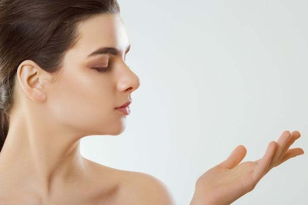 아름다움 얼굴. 자연스러운 makeup.woman 놀라운 보여주는 제품으로 아름 다운 여자