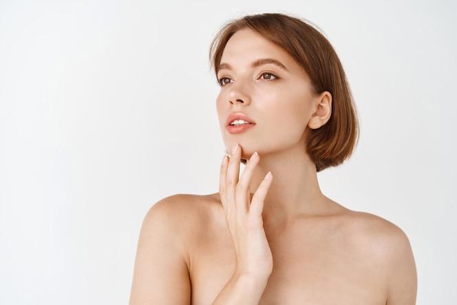 美顔。脇を見て、化粧をせずに自然な健康な肌に触れる美しい若い女性。裸の肩と輝く水和した顔を持つ少女。スキンケアのコンセプト