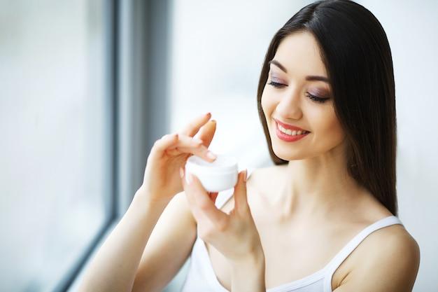 Beauty face care, woman applying cream on skin