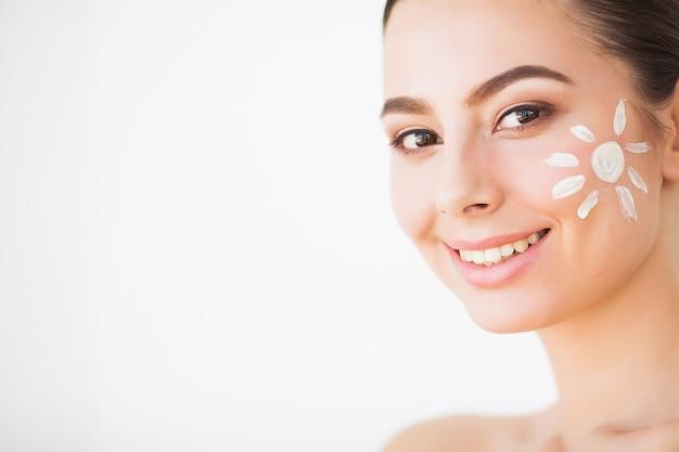 Beauty face care. woman applying cream on skin