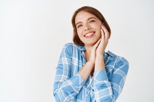 美顔。明るいメイクで自然な顔の肌に触れ、笑顔で白い歯を見せ、白い壁にのんびりと立っている幸せな若い女性モデル