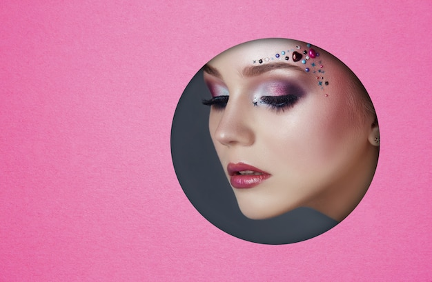 ピンクの紙の丸い穴に若い女性の美容顔メイク。美しいメイク、明るい目、輝く影、丸穴のふっくらした唇を持つ女性