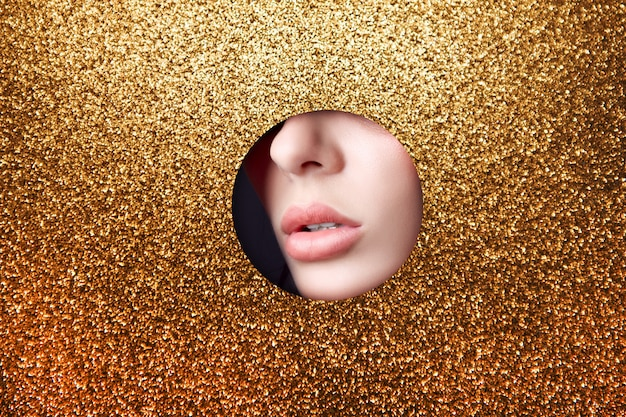 Beauty face makeup plump lips girl in round slit hole of yellow gold paper