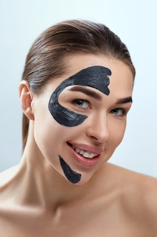 Beauty face mask. skin care face spa treatment . beautiful young woman with black mask of clay on face. moisturizer mask.