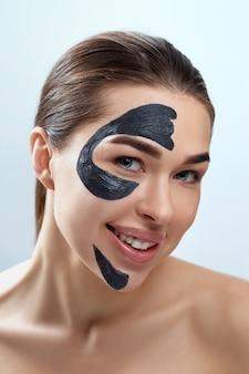 Маска для лица красоты. уход за кожей лица санаторно-курортное лечение. красивая молодая женщина с черной маской из глины на лице. увлажняющая маска.