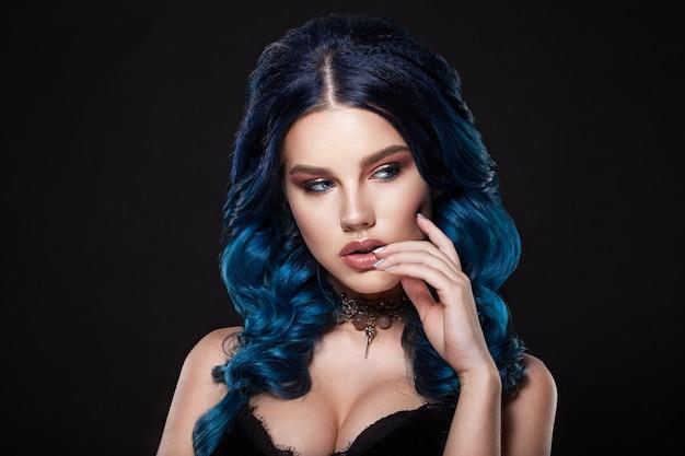Лицо красоты девушки с голубыми волосами и косой. профессиональный макияж, чистая кожа, снято на темном фоне.