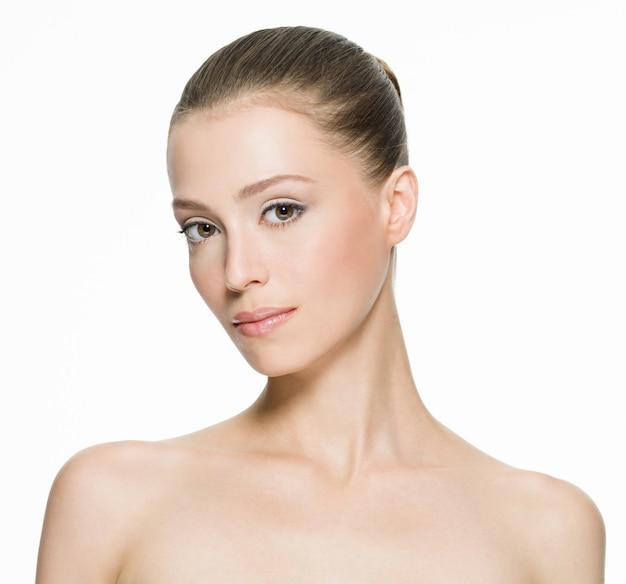 白で隔離ポーズのきれいな肌を持つ若い女性の美顔