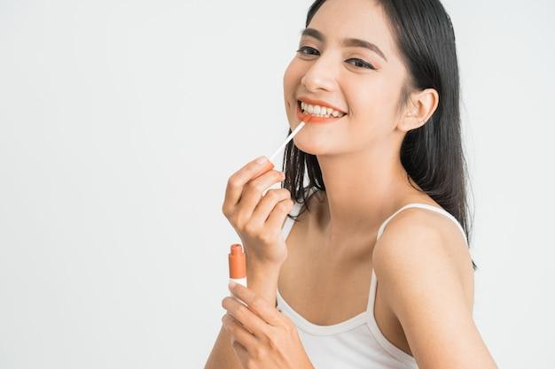 아시아 여자의 아름다움 얼굴. 그녀의 얼굴에 립스틱을 적용하는 여성의 초상화를 닫습니다.
