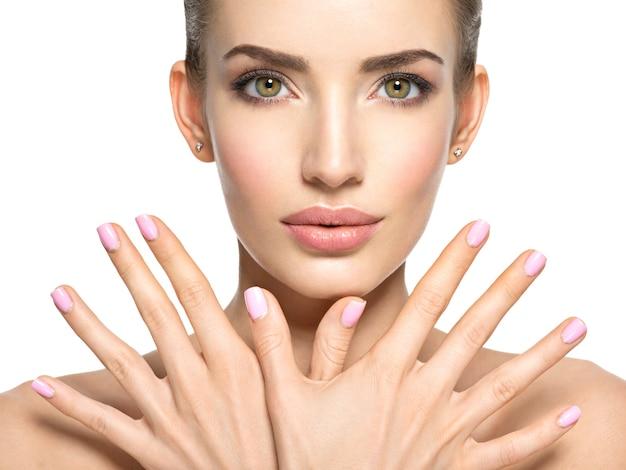 若い美しい女性の美しさの顔-白で隔離。素敵な指の爪を持つ女性。かなり若い女の子はピンクの爪で顔の前に手を示しています