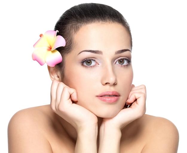 꽃과 젊은 여자의 뷰티 얼굴입니다. 미용 치료 개념. 흰색 배경 위에 초상화