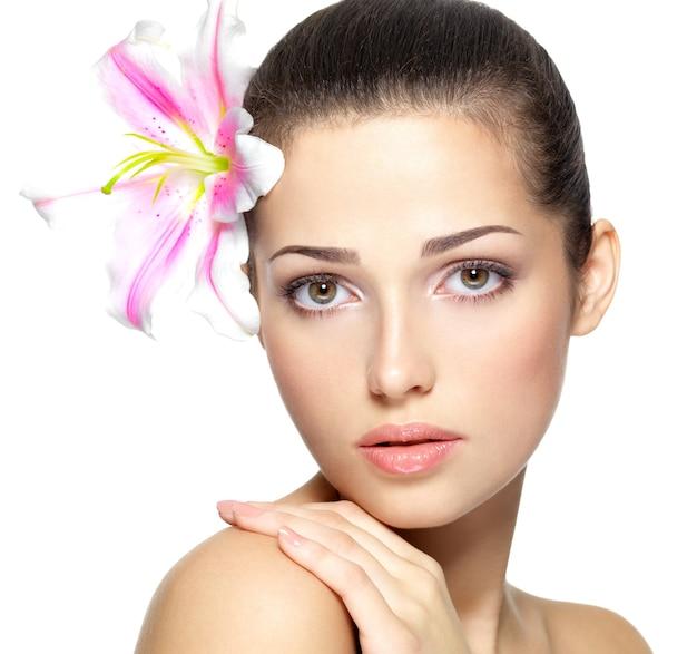 Сторона красоты молодой женщины с цветком.