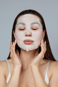 뷰티 페이스 스킨 케어. 아름 다운 여자는 얼굴에 천으로 보습 마스크를 적용합니다. 화장품 마스크와 여자 모델입니다. 페이셜 트리트먼트
