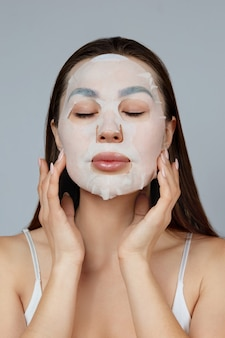 Beauty face skin care. beautiful woman apply a cloth moisturizing mask on face . girl model with cosmetic mask. facial  treatment