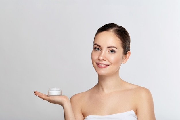 Beauty face skin care. beautiful woman with healthy smooth facial clean skin holding bottle cosmetic cream. model with beauty face. moisturizer facial treatment. cosmetology. spa.