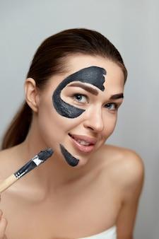 뷰티 페이스 스킨 케어. 웃는 여자는 클레이의 얼굴 스킨 케어 마스크를 적용합니다. 화장품 마스크와 소녀 모델. 페이셜 트리트먼트