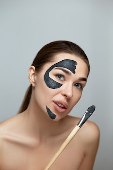 뷰티 페이스 스킨 케어. 여자는 얼굴에 찰흙의 검은 스파 페이셜 마스크를 적용합니다. 화장품 마스크와 여자 모델입니다. 페이셜 트리트먼트