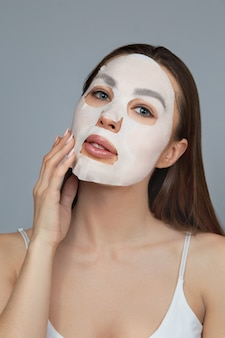 뷰티 페이스 스킨 케어. 여자는 얼굴에 천 보습 마스크를 적용합니다. 화장품 마스크와 여자 모델입니다. 페이셜 트리트먼트
