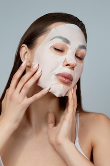 Beauty face skin care. woman apply a cloth moisturizing mask on face. girl model with cosmetic mask. facial  treatment