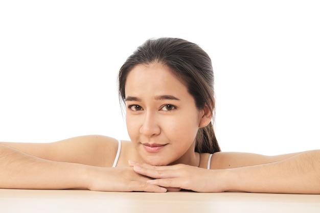 白い表面に分離された美しい魅力的なタイのアジアの女性モデルの肖像画に座っている美顔スキンケア女性。