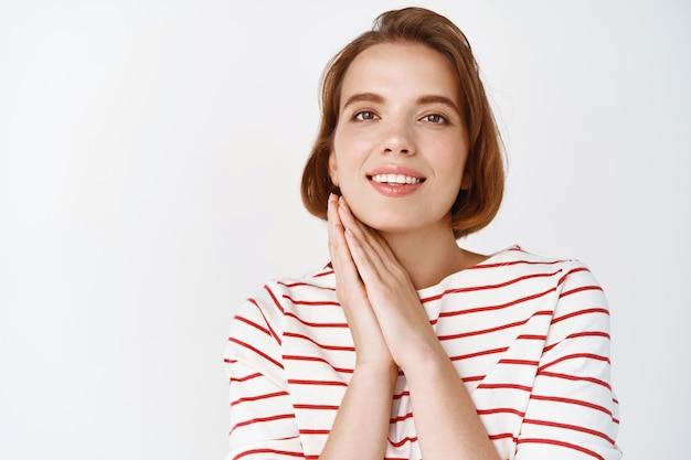美顔。短い髪、頬の近くで手をつないで、自然な肌、笑顔、白い壁にカジュアルな服を着て立っている優しい若い女性