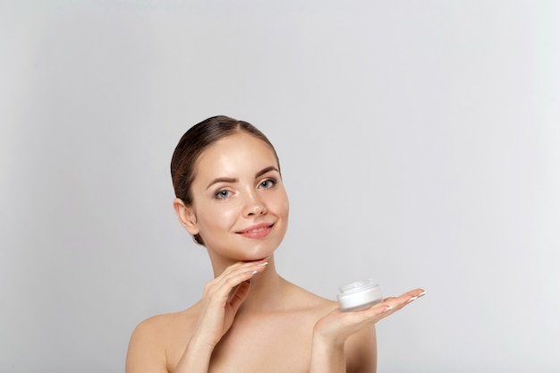 Beauty face of woman concept. skin care. portrait of female model  holding and applying cosmetic moisturizing cream and touch own face. skin protection. cosmetology. spa