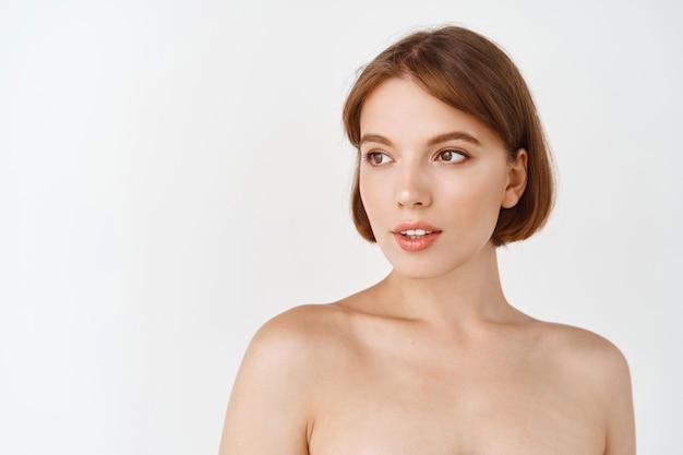 아름다움 얼굴입니다. 벌거 벗은 어깨, 자연스럽고 부드럽고 건강한 얼굴 피부를 가진 젊고 아름다운 여성이 빈 공간을 바라보고 있습니다. 소녀는 흠집이 없는 완벽한 얼굴, 스킨케어 개념을 가지고 있습니다.