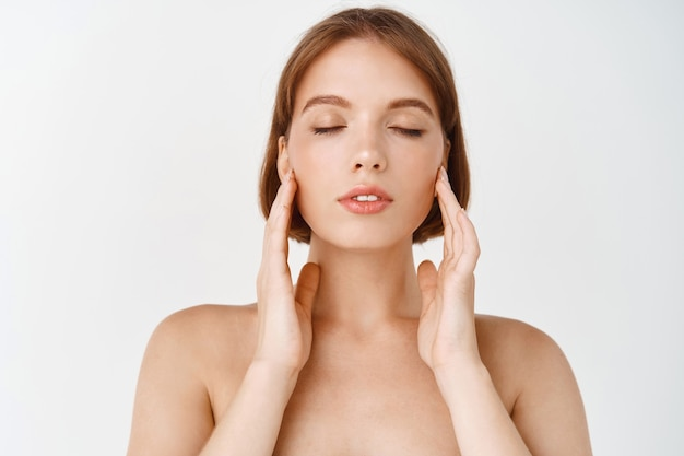 Beauty face. young woman rubbing creme in cheeks. girl with healthy hydrated facial skin, close eyes and gently youching natural face without make up, standing on white wall