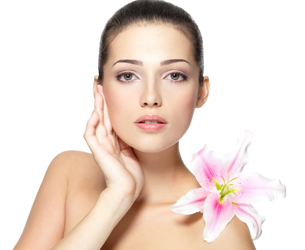 Fronte di bellezza della giovane donna con il fiore. concetto di trattamento di bellezza. ritratto su sfondo bianco