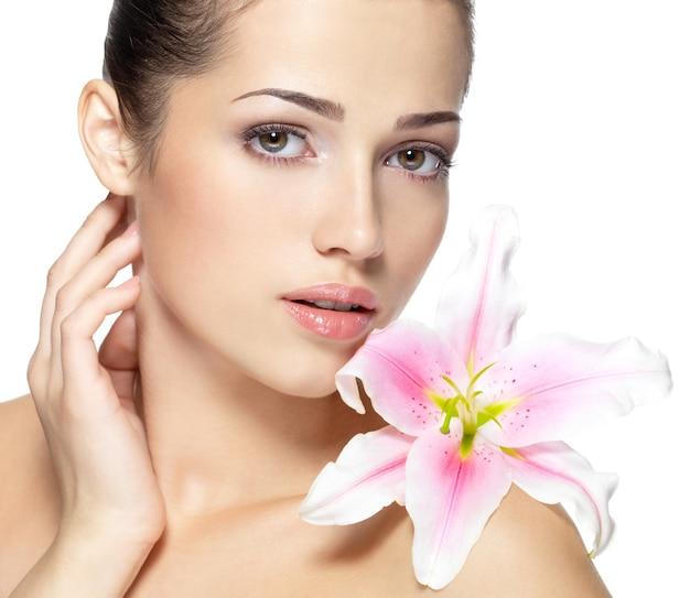 Fronte di bellezza della giovane donna con il fiore. concetto di trattamento di bellezza. ritratto sul muro bianco
