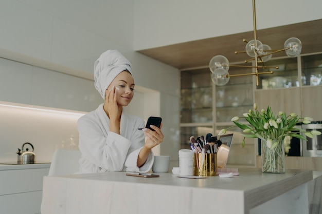 Beauty and facial care concept. young pretty woman in white bathrobe applying cosmetic product on face and looking in compact mirror, taking care of her skin while sitting in modern kitchen at home
