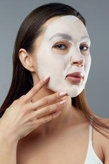 뷰티 페이셜 마스크. 얼굴에 천 보습 마스크와 아름 다운 여자. 피부 관리입니다. 화장품 스파 마스크. 페이셜 트리트먼트