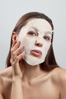 뷰티 페이셜 마스크. 얼굴에 천 보습 마스크와 아름 다운 여자. 피부 관리. 소녀 뷰티 모델은 그녀의 얼굴을 만집니다. 스파 마스크.