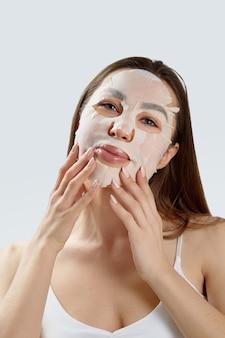 뷰티 페이셜 마스크. 얼굴에 천 보습 마스크와 아름 다운 젊은 여자. 피부 관리. 화장품 스파 마스크. 페이셜 트리트먼트