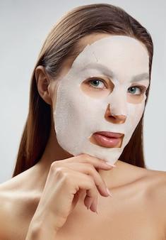 뷰티 페이셜 마스크. 얼굴에 천 보습 마스크와 아름 다운 젊은 여자. 피부 관리. 모델은 그녀의 얼굴을 만집니다.